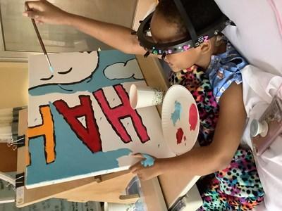 """Volando alto con Woodstock: La joven paciente Za'Nii Roundtree alardea de sus estupendas habilidades para pintar y colabora con un nuevo mural de Snoopy y Woodstock en el Gillette Children's en St. Paul, Minnesota, ciudad natal de Charles Schulz, el creador de Peanuts. Este es uno de los 70 murales que Peanuts Worldwide y la fundación sin fines de lucro Foundation for Hospital Art están donando a hospitales de todo el mundo, como parte de la iniciativa global """"Take Care With Peanuts"""" que se lanzó el 2 de octubre para el aniversario n.° 70 de Peanuts."""